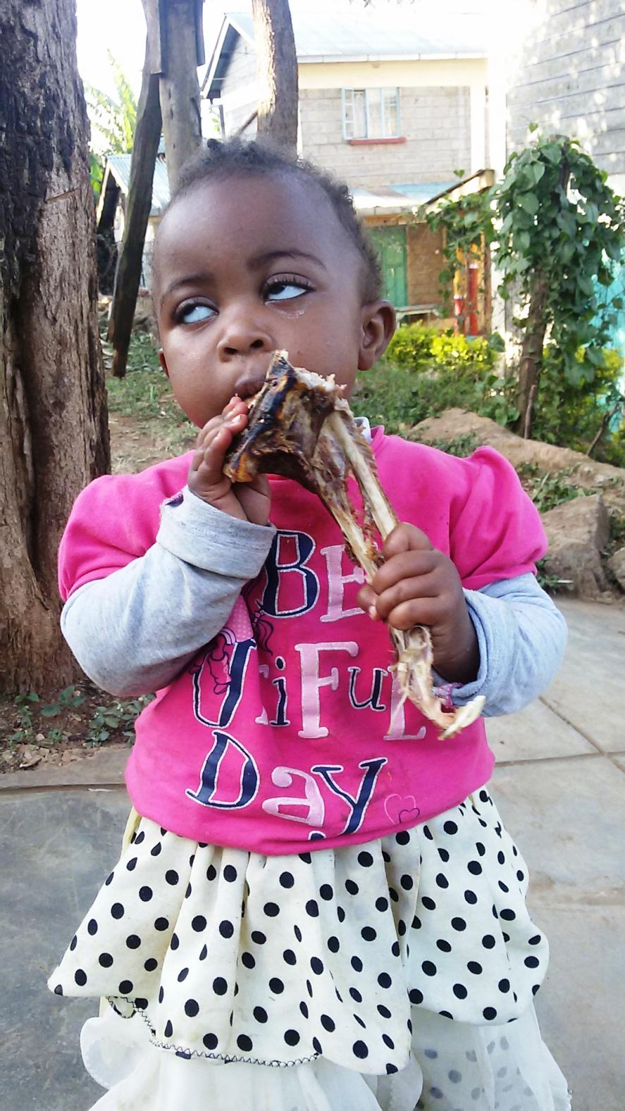 bambina di soweto mentre si gusta la capra